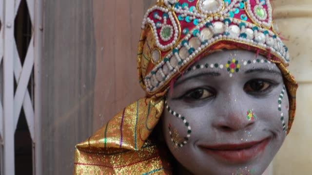 ヒンドゥー教の神ウィット化粧クラウンの衣装し、神の天恵を与える女性子供の手持ち服を着てをクローズ アップ - 舞台化粧点の映像素材/bロール