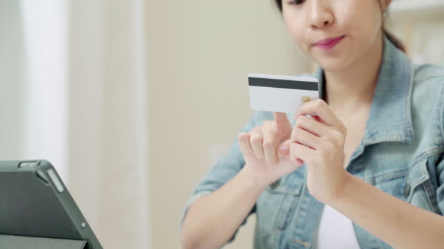 Close up Hand's attractive asian woman using credit card paying with tablet computer