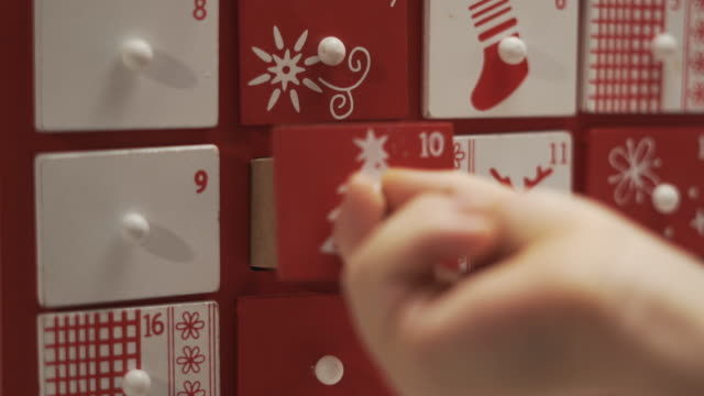 nahaufnahme hände kleiner junge nimmt süß aus adventskalender haus form. - advent stock-videos und b-roll-filmmaterial