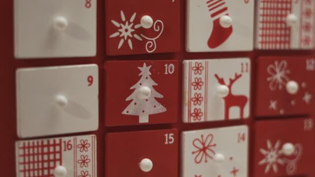 vidéos et rushes de fermez-vous vers le haut des mains petit garçon prend doux de la forme de maison de calendrier de l'avent. - calendrier de l'avent