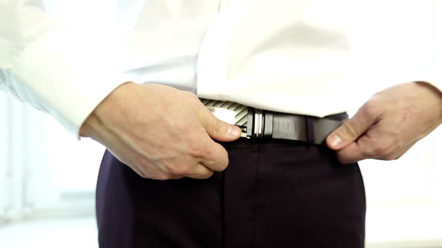 Close up. Hands of a man can't open the belt. video