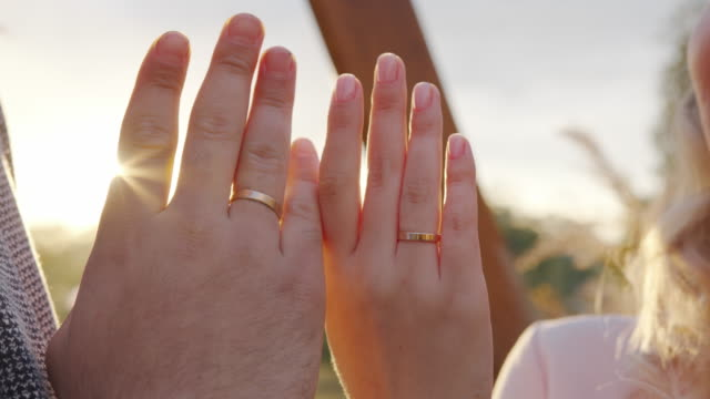 Close up. Hands of man and woman with wedding rings, groom and bride standing on ceremony.