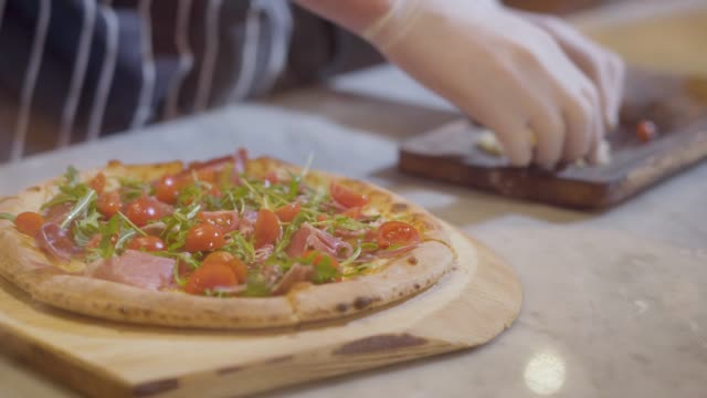 Close up hands of pizza maker is cooking pizza at modern restaurant kitchen.