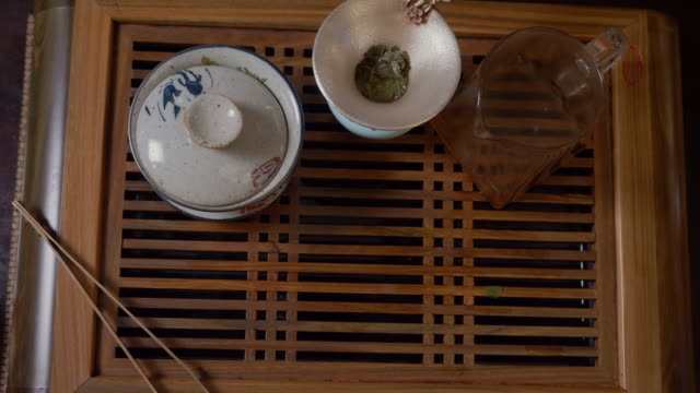 Close up hands of tea lover taking green tea cup from wooden table top view