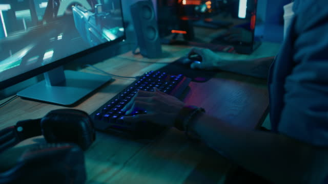 Close Up Hands Shot Showing a Gamer Pushing the Keyboard Buttons while Playing an Online Shooter Video Game. Keyboard Led Lights Change Color in Rainbow Spectrum. Gamer is Wearing a Bracelet. Close Up Hands Shot Showing a Gamer Pushing the Keyboard Buttons while Playing an Online Shooter Video Game. Keyboard Led Lights Change Color in Rainbow Spectrum. Gamer is Wearing a Bracelet. Room is Dark. Shot on RED EPIC-W 8K Helium Cinema Camera. gamer stock videos & royalty-free footage