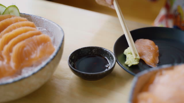 Close Up Hands with Chopstick Picking Salmon Sashimi Dipping into Soybean and Wasabi in Japanese Restaurant.