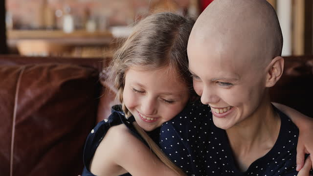 Close up happy little daughter hugs mother cancer patient Close up little daughter hugs mother cancer patient. Happy family sit indoor embracing feeling grateful for remission, express love, kid girl supporting mom, encourage her, hoping in recovery concept cancer patient stock videos & royalty-free footage
