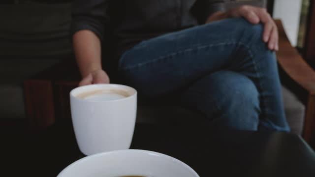 schließen sie herauf bild zweier menschen klirren milchkaffee tassen im café - milchkaffee stock-videos und b-roll-filmmaterial