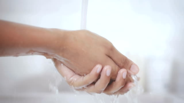 Close up lathering hands with soap hand sanitizer gel then water washing in toilet to prevent Coronavirus pandemic