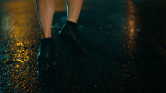 雨の路上で、ジョギング スポーツ服で運動若い男の脚のショットを閉じる。彼は、暗い都市環境下での brindge バック グラウンドで車で走っています。 - 耐久力点の映像素材/bロール