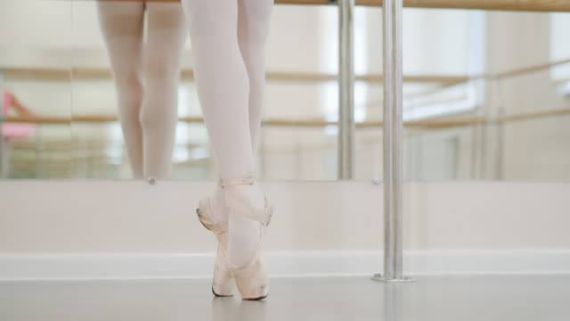 close up legs of ballerina in pointe shoes. training before performance. woman practicing in classical ballet in tutu dress in gym or ballet hall near barre. performing. 4k - studio tańca filmów i materiałów b-roll