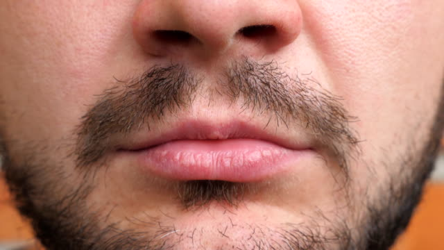Close up lips of young bearded man. Detail view on closed male mouth. Portrait of handsome guy with serious and confident expression on the face. Front view