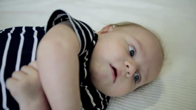 stockvideo's en b-roll-footage met close-up. kleine baby liggend op kant en draaide over op de rug. - background baby