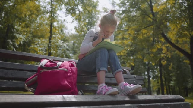 close up little beautiful school girl drawing with colored pencils, sitting on a bench in sunny park. slow motion shot - bench stock videos & royalty-free footage
