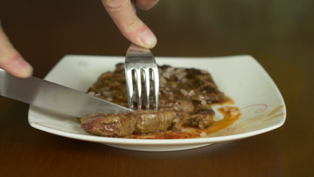 Close up locked shot of steak. Hands with knife and fork take part of meat steak from plate. video