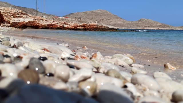 close up low angle shot of aegean sea in halki ( chalki ) island in the summer against rusty rocky hills - isole egee video stock e b–roll