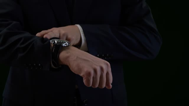 Close up luxury watch on male hand isolated on black background Close up luxury watch on male hand isolated on black background. Expensive watch on male wrist. Business man in black suit looking on wristwatch wristwatch stock videos & royalty-free footage