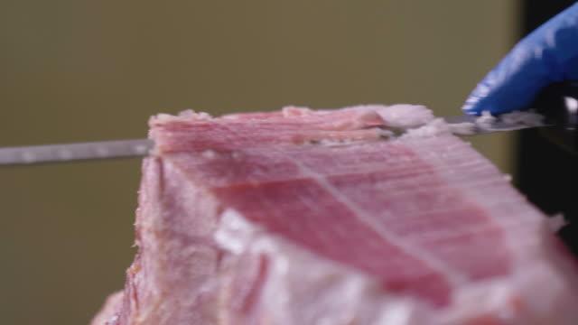 primo tempo macro di uno chef che taglia una fetta di prosciutto, di ottima qualità, con il coltello secondo la tradizione. - crudo video stock e b–roll