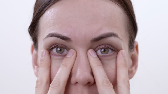 stockvideo's en b-roll-footage met close-up macro van brunette vrouw doen oefening voor het versterken van de onderste oogleden. geïsoleerd op de witte achtergrond. - ooglid