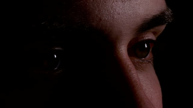 Close up macro of young man eyes looking and searching in the dark video