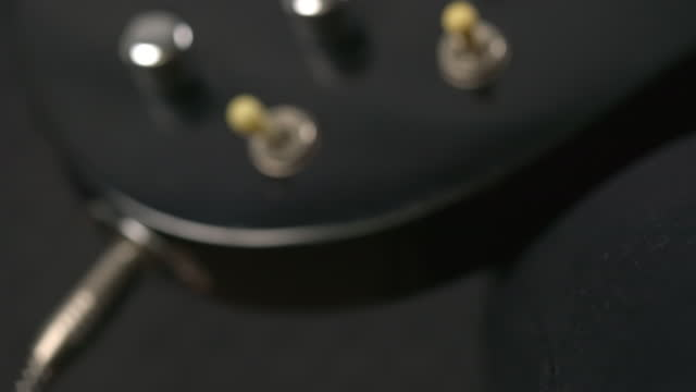 Close up macro shot of African man's hand connecting electric guitar. Plugging audio cable in guitar. String instruments