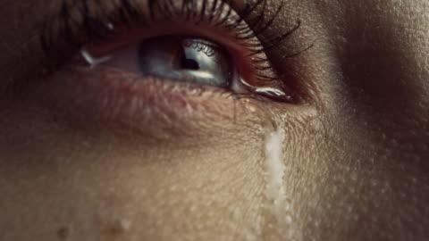 vidéos et rushes de fermez-vous vers le haut macro zoom shot d'un oeil pleurant. jeune femelle beatiful avec la pigmentation de couleur bleue claire normale, jaune et brune sur l'iris. mascara est appliqué sur les cils. les larmes coulent. - personnes belles