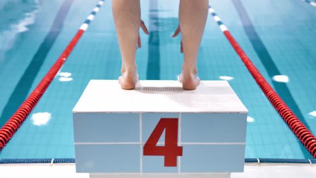 vidéos et rushes de bouchent nageur professionnel de pieds mâles vue arrière plongée ou en sautant de bloc en piscine - starting block