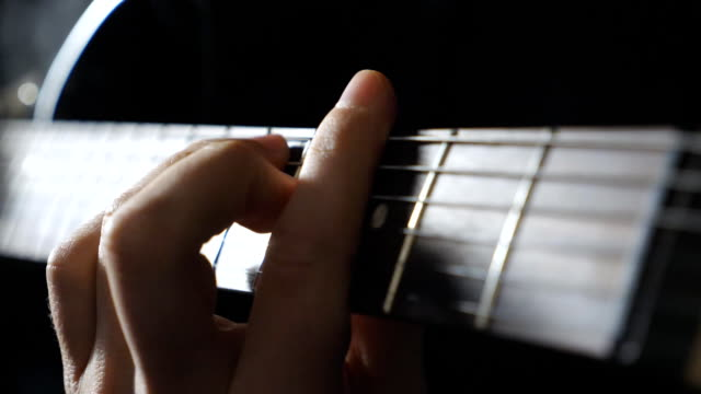 close up male fingers of guitarist strumming the strings. hand of guy performing solo of rock music. arm of musician playing on electric guitar. adult man composing a new melody. slow motion - гитара стоковые видео и кадры b-roll