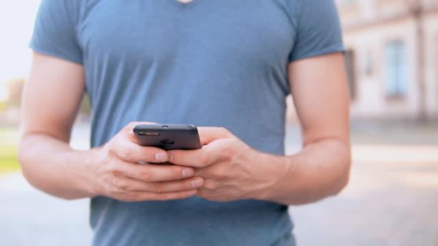 stockvideo's en b-roll-footage met close-up van mannelijke handen met mobiele - t shirt