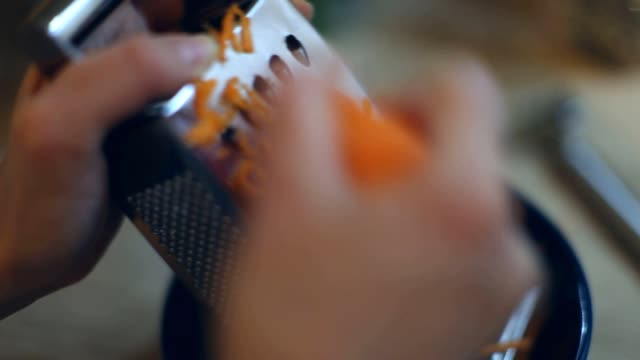 Close up male hands rubs carrots on grater Close up male hands rubs carrots on grater carrot stock videos & royalty-free footage