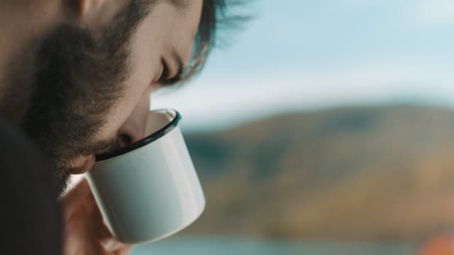 vídeos y material grabado en eventos de stock de primer plano, hombre tomando café y leyendo en el viaje de campamento - café bebida