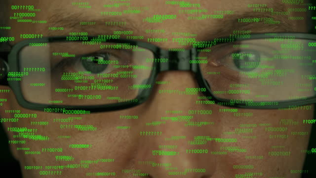 Close up man face in glasses. Eyes motion rapidly randomly. Binary code numbers stream from top in front of eyes of caucasian man. Modern techology futuristic concept. video