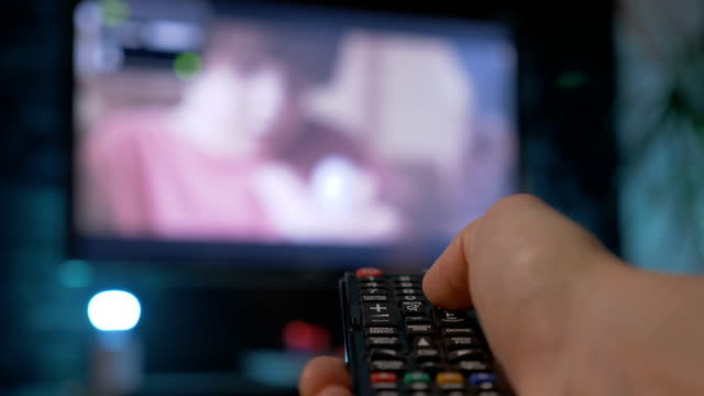 Close up man hand holding the TV remote control and changing channels. video