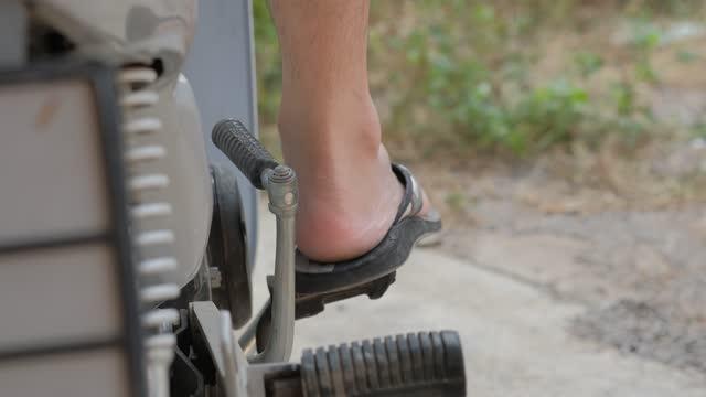 Close up Man Leg Trying to Start Engine Motorcycle