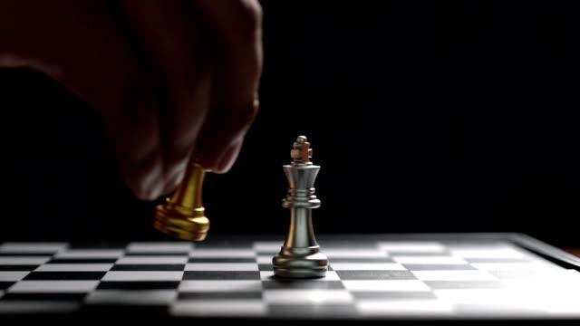 nahaufnahme mann bewegte goldene königsschach besiegen feind auf schachbrett-sieger und siegeskonzept, strategieplanungsgeschäft slowmotion - könig schachfigur stock-videos und b-roll-filmmaterial