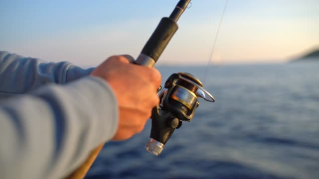 4k close up man reeling in fishing line, real time - rybak filmów i materiałów b-roll