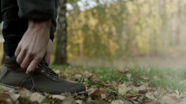 Close up, man tying shoelaces on autumnal leaves