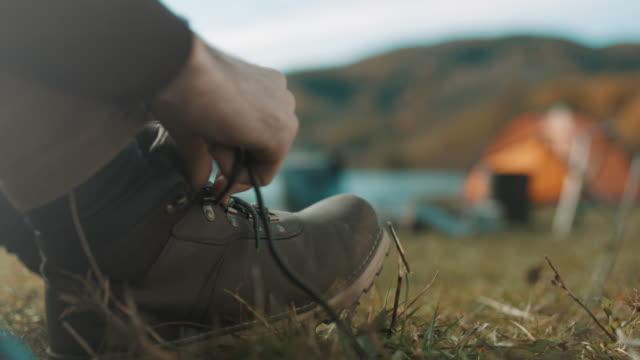 vidéos et rushes de gros plan, homme attachant lacets - bottes