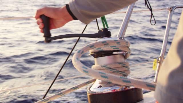 vídeos y material grabado en eventos de stock de cerca de 4k hombre con manivela, apretando la cuerda en velero, cámara lenta del aparejo - manija