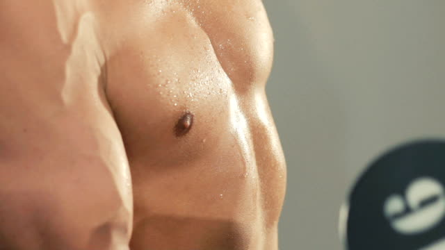 Close up man's body training with the weight in gym. Slowly video