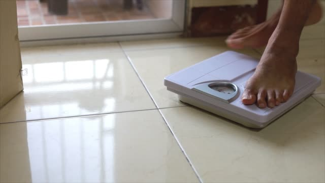 Close up man's feet standing on body weight scales for measure weight loss.Weighing scale to healthy slimming concept.