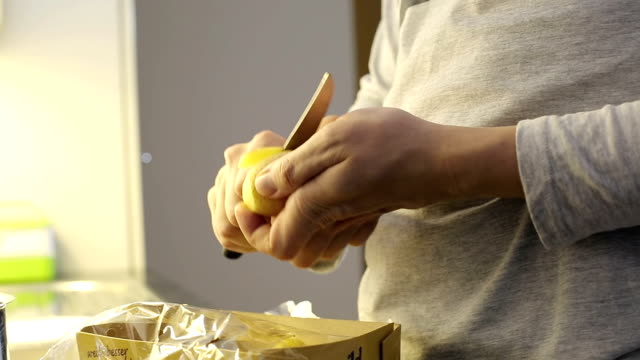 Close up. Man's hand peeling potatoes with knife. video