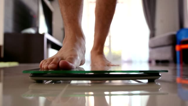 Close up men barefoot legs stepping on flooring scales for weighting in living room.