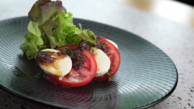 Close up motion of caprese on plate.