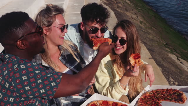 Close up multi-ethnic friends eating takeaway pizza by riverside