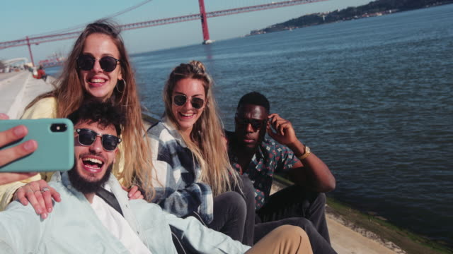Close up multi-ethnic friends taking selfie with smartphone by riverside