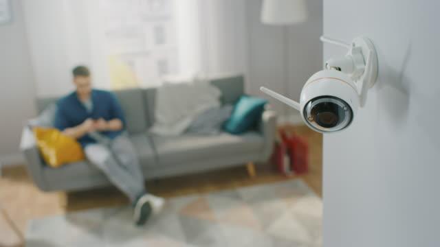 stockvideo's en b-roll-footage met close up object shot van een moderne wi-fi surveillance camera met twee antennes op een witte muur in een gezellig appartement. de mens zit op een bank op de achtergrond. - alarm, home,