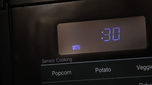Close up of 30 Seconds Entered and Counting Down Cooking Time on a Black Digital Display Microwave