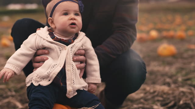 Close up of a baby sitting on a pumpkin at a pumpkin patch, with her dad holding her up