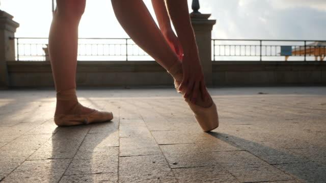 vídeos de stock, filmes e b-roll de perto dos pés de uma bailarina como ela corrige pointe sobre o aterro de pedra. pés das mulheres em sapatilhas. bailarina se preparando para pas de balé clássico. câmera lenta. clarão, tiro de cardan - bailarina